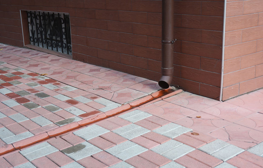 Downspout Feeding Into Drain Pipeline in Pavement or Foundation